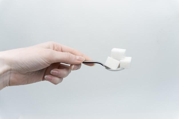 Cubos de açúcar branco na colher
