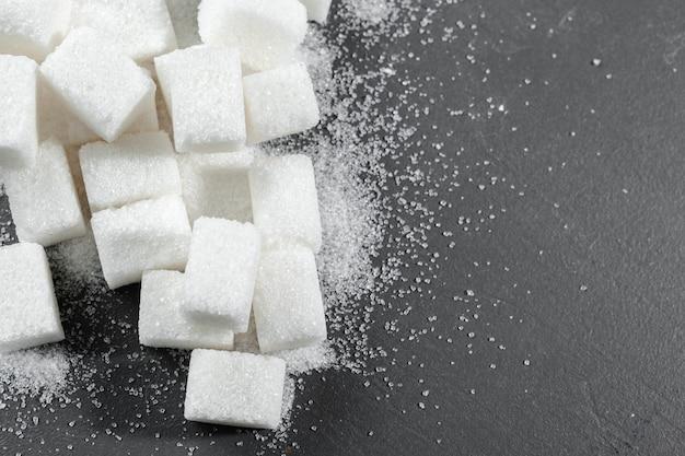 Cubos de açúcar branco sobre fundo preto close-up