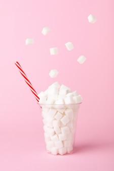 Cubos de açúcar cair no copo de rosa pastel