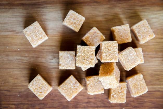 Cubos de açúcar de cana marrom em uma tábua de madeira. vista do topo