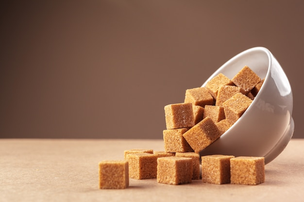 Cubos de açúcar de cana marrom sobre um fundo marrom claro