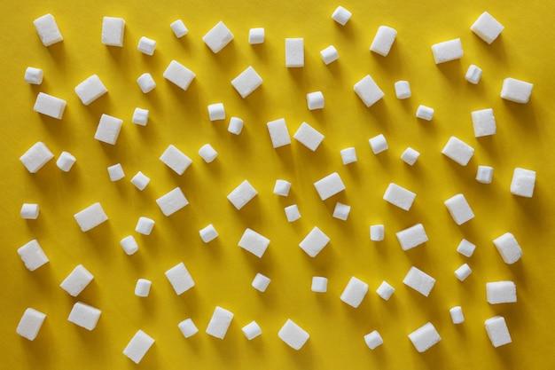 Cubos de açúcar e marshmallows em fundo amarelo