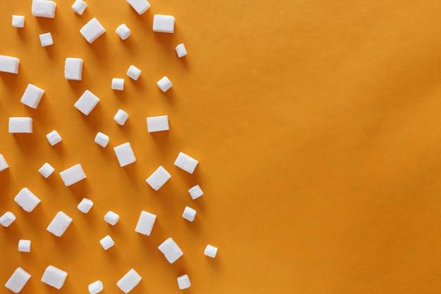 Cubos de açúcar e marshmallows em fundo laranja