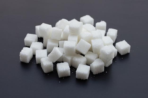 Cubos de açúcar em fundo escuro.