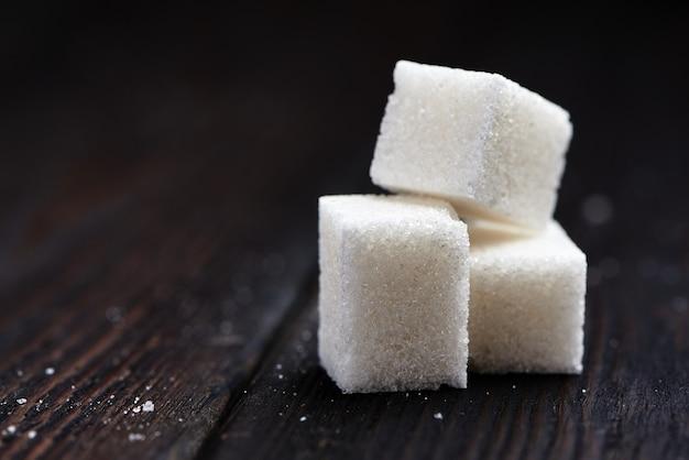 Cubos de açúcar em um fundo de madeira