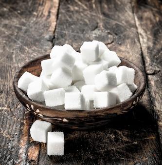 Cubos de açúcar em uma tigela sobre um fundo de madeira