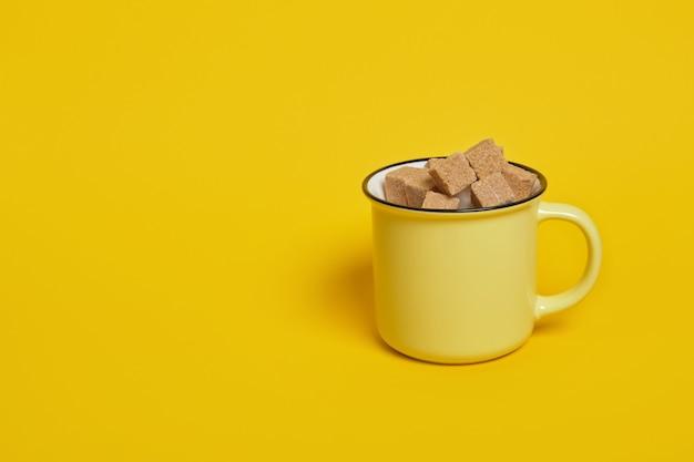 Cubos de açúcar mascavo de cana em um copo amarelo em uma superfície amarela copie o espaço