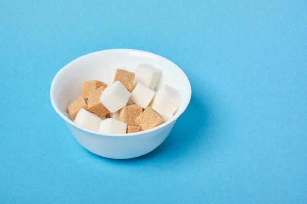 Cubos de açúcar mascavo e branco em uma tigela branca em uma superfície azul copie o espaço
