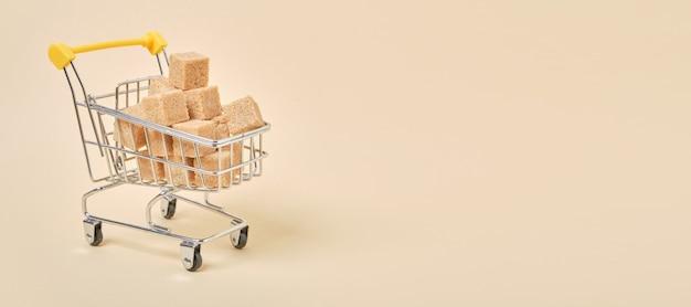 Cubos de açúcar mascavo em um carrinho de compras em miniatura em uma superfície bege