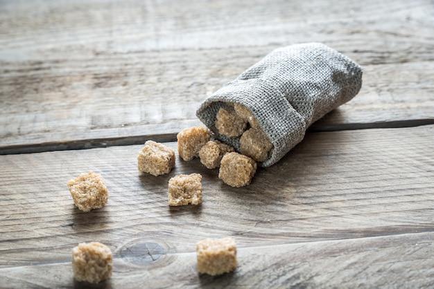Cubos de açúcar mascavo na mesa de madeira