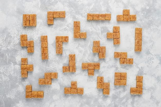 Cubos de açúcar mascavo no concreto, vista superior