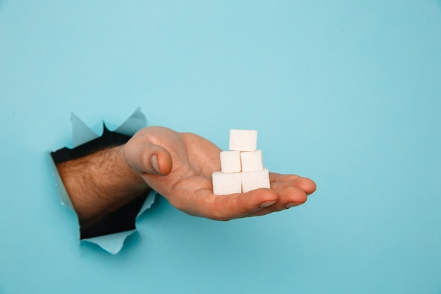 Cubos de açúcar na mão de um buraco rasgado em papel azul