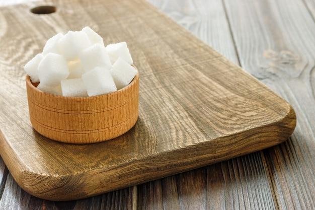 Cubos de açúcar na tigela na mesa de madeira. cubos de açúcar branco na tigela