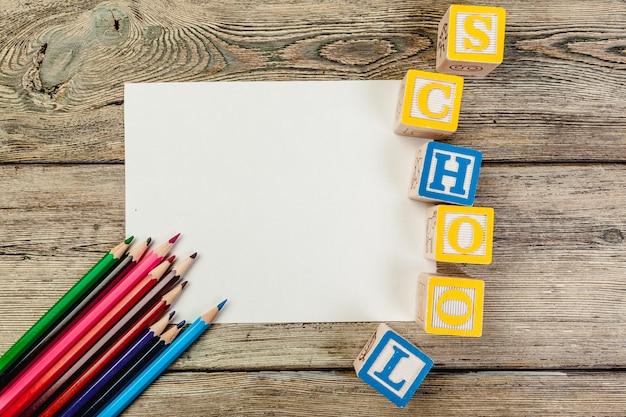 Cubos de brinquedo com letras na mesa de madeira com folha de papel em branco para desenho