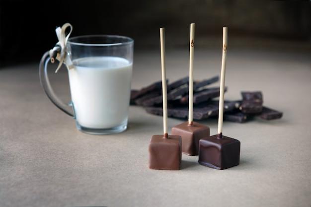 Cubos de chocolate no palito com copo de leite e cacau aromático e chocolate no fundo marrom. cacau quente com leite em copo de vidro transparente, cubos de chocolate partidos de avelã