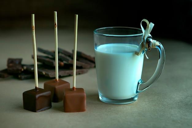 Cubos de chocolate no palito com uma xícara de leite e cacau aromático e chocolate no fundo marrom, close-up. cacau quente com leite em copo de vidro transparente, cubos de chocolate partidos de avelã