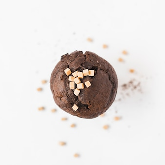 Cubos de doces de caramelo no bolinho marrom contra fundo branco