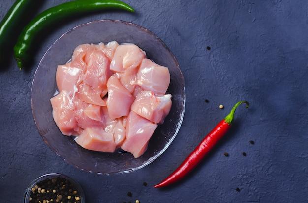 Cubos de frango cru na tigela e pimenta