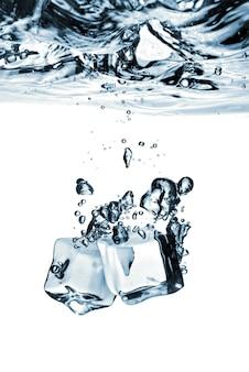Cubos de gelo caídos na água com respingos isolados no branco