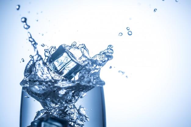 Cubos de gelo caindo no copo com salpicos de água close-up