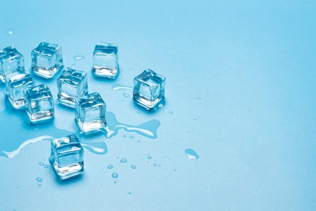 Cubos de gelo com água sobre um fundo azul. conceito de gelo para bebidas.