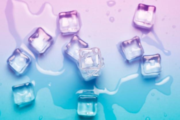 Cubos de gelo com água sobre um fundo azul. luz abstrata. conceito de gelo para bebidas.