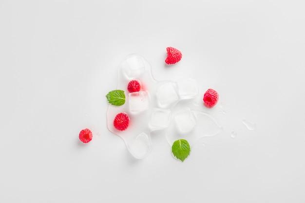 Cubos de gelo com framboesas e folhas de hortelã na mesa de madeira. cubos de gelo hidratantes para a pele caseira