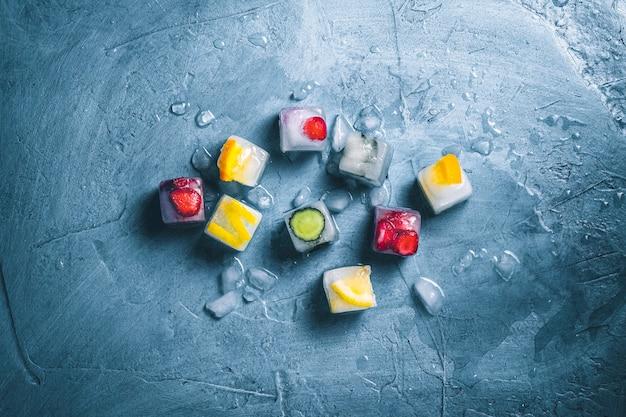 Cubos de gelo com frutas e gelo quebrado em um fundo azul de pedra. hortelã, morango, cereja, limão, laranja. vista plana, vista superior
