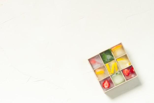 Cubos de gelo com frutas em molde de silicone em uma superfície de pedra branca. conceito de gelo de frutas, saciando a sede, verão. vista plana, vista superior