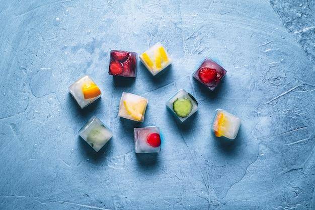 Cubos de gelo com frutas em uma superfície de pedra azul. hortelã, morango, cereja, limão, laranja. vista plana, vista superior
