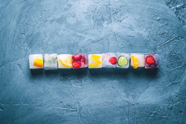Cubos de gelo com frutas em uma superfície de pedra azul. linha. hortelã, morango, cereja, limão, laranja. vista plana, vista superior