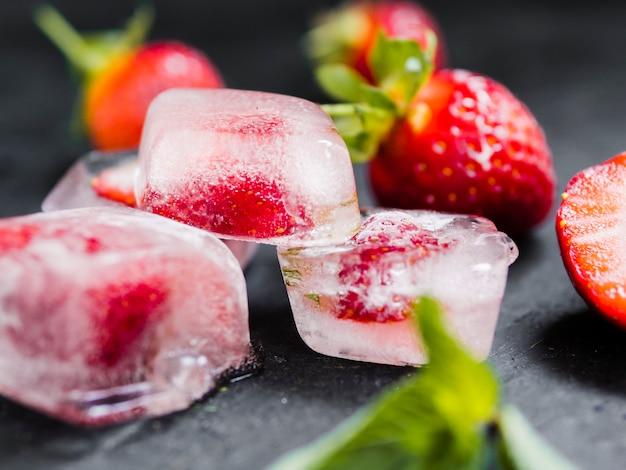 Cubos de gelo com frutas na mesa escura