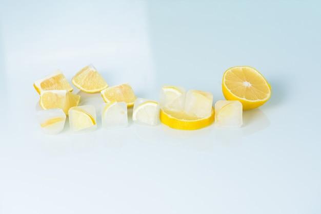 Cubos de gelo cosméticos com limão e vitamina c para cuidar da pele em um fundo azul claro