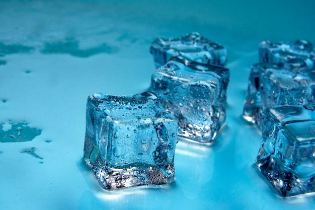 Cubos de gelo / cubos de gelo com umas gotas da água isoladas no fundo azul / espaço da cópia para o texto / ascendente próximo.