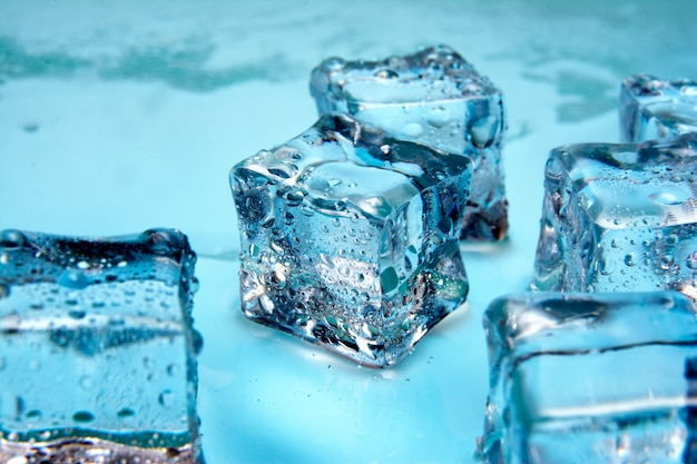 Cubos de gelo / cubos de gelo molhado no fundo brilhante azul / close up / espaço de cópia de texto