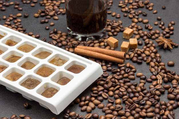 Cubos de gelo de café. copo com café. grãos de café espalhados na mesa, anis estrelado, paus de canela e pedaços de açúcar mascavo.