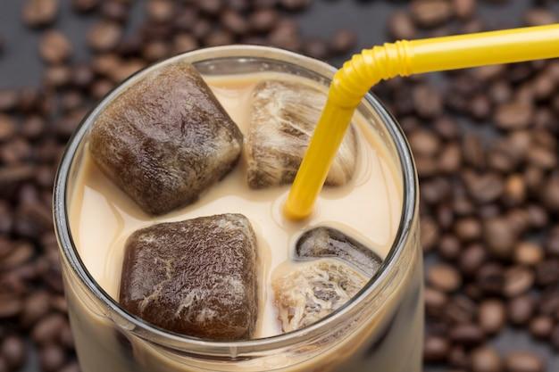Cubos de gelo de café em copo com café e leite.