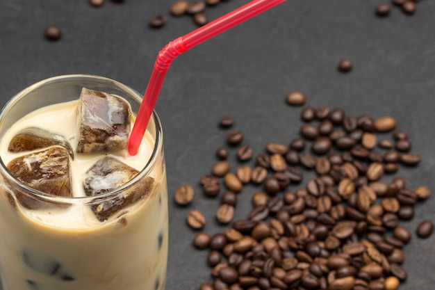 Cubos de gelo de café em copo com leite e canudo vermelho.