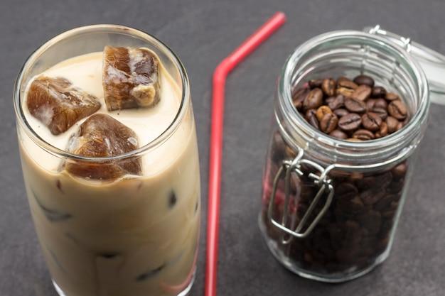 Cubos de gelo de café em copo com leite. grãos de café em potes de vidro.