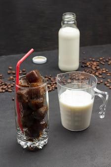 Cubos de gelo de café em um copo com canudo vermelho, leite em copo medidor, leite