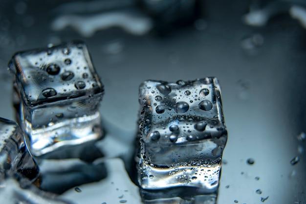Cubos de gelo derretendo com gotas de água sobre um fundo mirrow.