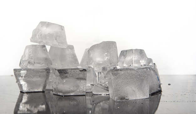 Cubos de gelo derretendo na superfície reflexiva escura, fundo branco, foco seletivo.