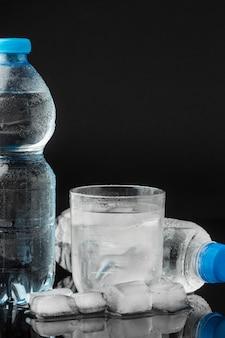 Cubos de gelo e água de vista frontal