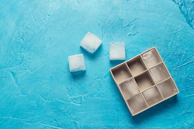 Cubos de gelo e molde de silicone em um fundo de pedra azul. conceito de produção de gelo. vista plana, vista superior