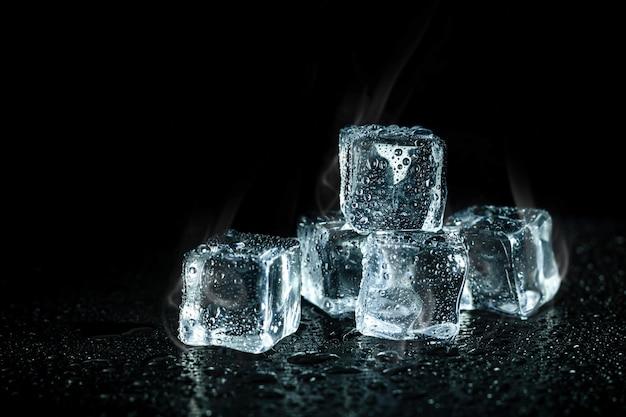 Cubos de gelo e resfriamento de fumaça na mesa escura. blocos de gelo com bebidas frias.