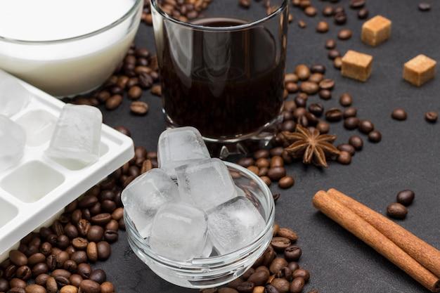 Cubos de gelo em pires, copo com café, xícara com leite. no fundo preto, grãos de café, pau de canela, anis estrelado.