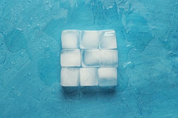 Cubos de gelo em um fundo de pedra azul. forma da praça. conceito de produção de gelo. vista plana, vista superior
