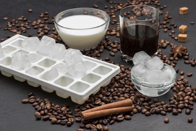 Cubos de gelo em uma tigela de vidro, copo de leite e copo de café. grãos de café e paus de canela