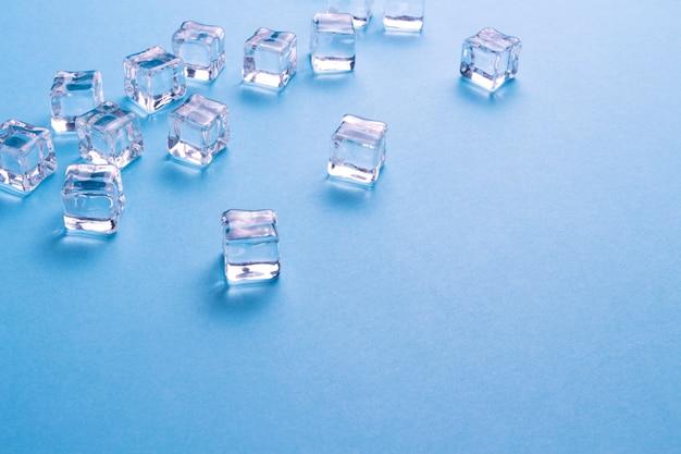 Cubos de gelo espalhados sobre um fundo azul claro