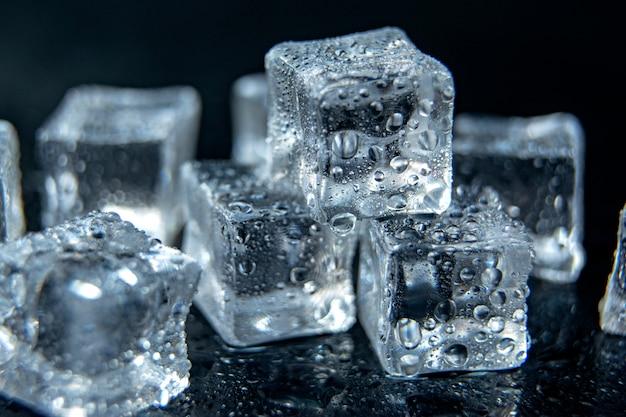 Cubos de gelo no fundo de vidro isolado preto / conceito gelado